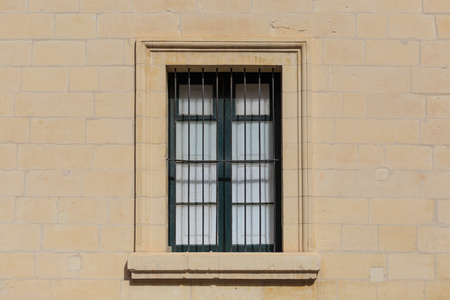 Malta, Valletta. Facade of yellow limestone house with closed window with metal grid, that provides security. Close up view. Stock Photo
