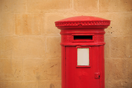 Traditional, aged, British letterbox in red color. Mailbox that receives the letters. Light orange limestone wall for background. Space for text, close up view.