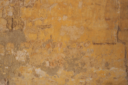 Weathered yellow painted wall background, partially faded. Corroded, peeled, vintage, blank wall for backdrop. Close up view with details. Stock Photo