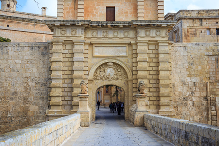 Malta, Mdina entrance gate. Tourists cross the footbridge to visit the historic fortified town. Destination for vacation and tour.