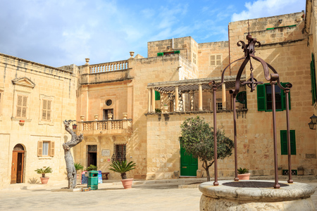 Mdina, Malta. Well at Misrah Mesquita square and traditional facade limestone buildings and blue sky background. Editorial