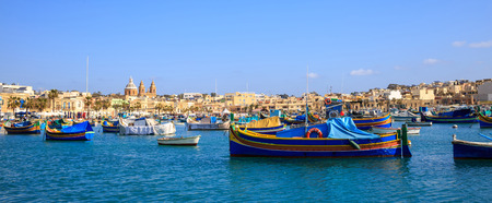 Malta, Marsaxlokk historic harbor full of boats. Destination for vacation, relaxing and fishing. Blue sky and village background. Close up view, banner.