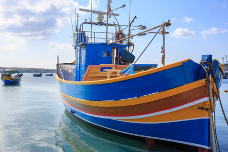 Traditional colorful fishing boat, luzzu, anchored at Marsaxlokk, the historic port of Malta. Blue sky with clouds and village background. Close up view with details. Stock Photo