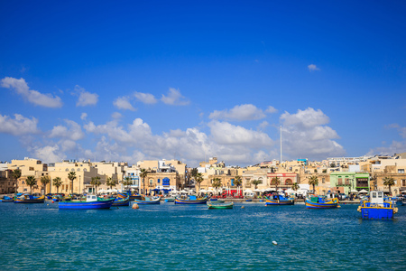 Marsaxlokk historic port full of boats in Malta. Blue sky with few white clouds and village background. Destination for vacation, relaxing and fishing. Panoramic view. Stock Photo