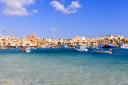 Marsaxlokk historic port with many boats in transparent sea, Malta. Blue sky with few white clouds and village background. Destination for vacation, relaxing and fishing.
