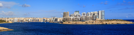 Malta, Valletta. Sliema town with multistorey waterfront buildings, blue sea and blue sky with few clouds background. Panoramic view, banner. Stock Photo