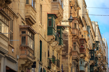 Malta, Valletta, traditional sandstone buildings with colorful wooden windows on covered balconies. Blue sky with clouds background. Close up view.