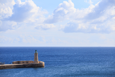St. Elmos lighthouse at Valletta, Malta. Breakwater of grand harbour between blue sea and cloudy sky background. Stock Photo