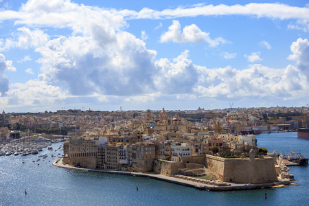 Malta, Valletta. Senglea, a fortified grand harbour that is surrounded of many boats and ships, under a blue sky with few clouds. Panoramic view, town background.