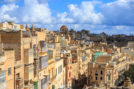 Malta, Valletta. Capital with tall traditional limestone buildings and covered balconies, under a blue sky with few clouds. Stock Photo