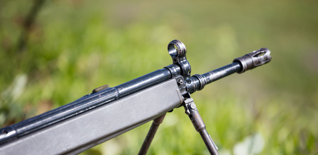 Firearm handgun on easel, stable for marking the target. Front side of weapon with close up view on blurred nature background.