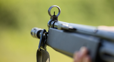 Firearm handgun in man s hand who marks the target. Front side of weapon with close up view on blurred nature background. Stock Photo