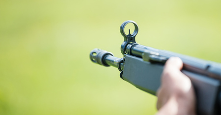 Firearm handgun in man s hand who marks the target. Front side of weapon with close up view on blurred nature background, space for text.