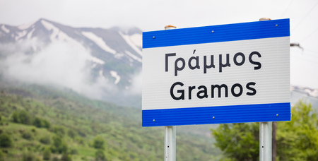 Pindus, Gramos the snowy mountain in west Greece. Destination for mountaineering. Blurred mountain and nature background. Close up view of sign with the mountains name, panoramic. Stock Photo