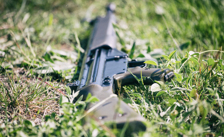 Anti-war concept. Firearm handgun lays down on green grass because soldier deny to kill. Close up view of the weapon on blurred nature background.