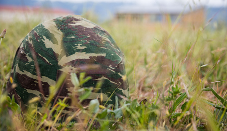 Military camouflage helmet putted down on the ground. Anti-war symbol. Soldier got tired of war. Close up front view, blurred nature background, space for text.