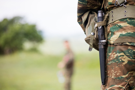 Soldier body who standing with camouflage clothing and knife in his belt. Close up behind view, blurred soldier and nature background, space for text.