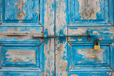 Wooden peeled blue door, locked, aged for backdrop. Old entrance with rusty latch and padlock. Closeup.