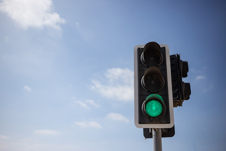 Green traffic light. Signal that it is safe to go on the way. Blue sky with few clouds background. Close up under view, space for text. Stock Photo