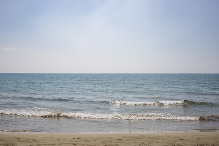 Sandy beach, sea with low waves, blue sky with few clouds for backdrop. Summer destination. Close up view.