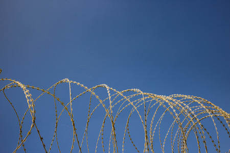 Wire circle mesh metal fence, sharp with razors, barbed, provides security and warning of danger. Blue sky backdrop, closeup. Stock Photo
