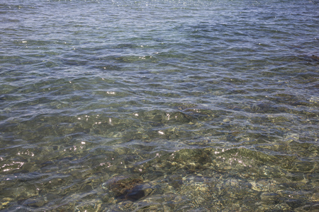 Transparent clear sea at Cyprus island. Crystal water with pebbles and suns reflection background.