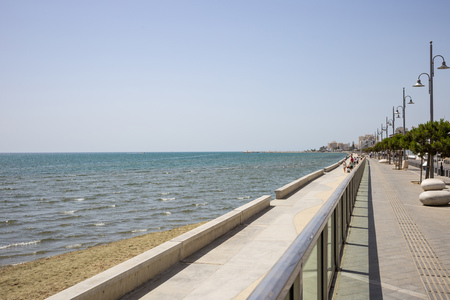 Cyprus, Larnaca city. Stone path for promenade around the sea. Harbor, beach, building, blue sky background.