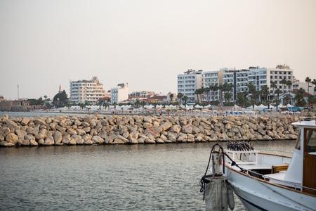 Breakwater of stones at Cyprus, Larnaca. Summer destination. Beach, sea, town, blue sky background.