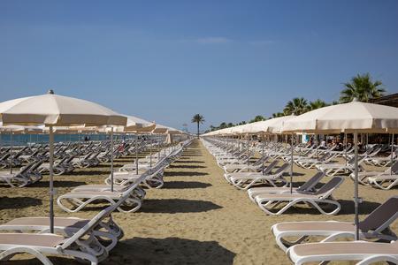 Mackenzie sandy beach at Larnaca, Cyprus. Sun loungers and umbrellas next to sea. Blue sky backdrop, closeup view.