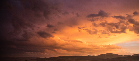 Dusk or dawn concept. Red cloudy sky at sunset, mountain range, banner, copy space, wallpaper. Stock Photo