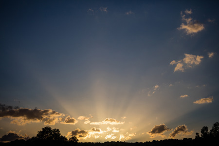 Sunrays light concept. Sunrise sunbeams through the clouds from the horizon, copy space, wallpaper. Stock Photo