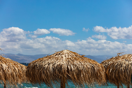 Straw umbrellas closeup, windy beach and blue sky with clouds background Stock Photo