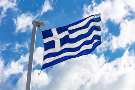 Greek flag on flagpole waving on blue sky background Stock Photo