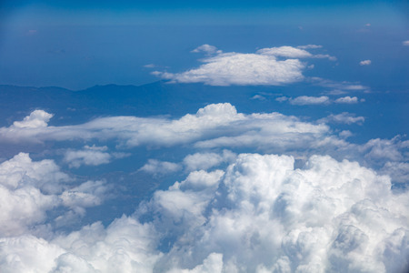 White fluffy clouds background hanging on blue sky over mountain. Aerial photo from airplanes window. Stock Photo