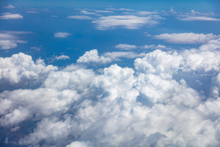 Blue sky, white fluffy clouds cover the earth background. Aerial photo from airplanes window.