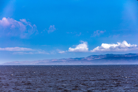 Windy day, waves on the sea and blue sky with white clouds. Mountains and greek island background. Stock Photo