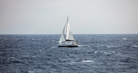 Sailboat travels with wind help, against the waves. Ripple sea, blue sky background.