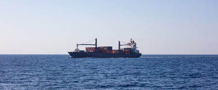 Container ship for international transport sail full of cargo. Sea commerce, blue sky background, banner.