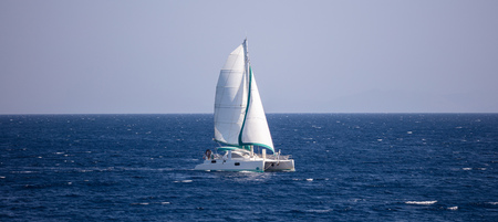 Sailboat travels with wind help, in calm sea. People enjoy the sailing, blue sky background, banner. Stock Photo