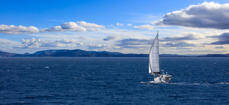 Sailboat travels with wind help, in calm sea. People enjoy the sailing, cloudy sky and mountains background, banner. Stock Photo