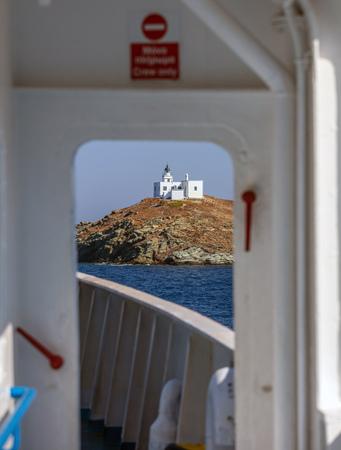 View from ships door of lighthouse and agios Nikolaos church on rocky land. Kea,Tzia island, Greece. Blue sky background. Stock Photo