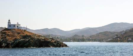 Lighthouse and agios Nikolaos church on rocky land. Kea,Tzia the sunny island, Greece. Blue sky background, banner.