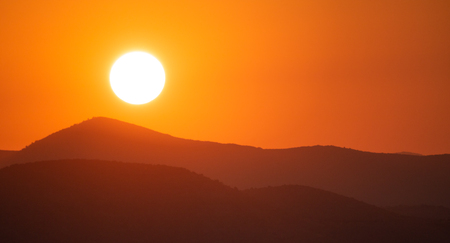 Sunset over mountains silhouette.