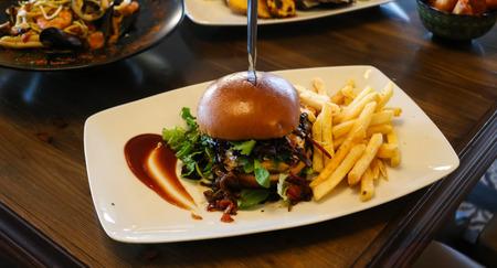 Hamburger with french fries on white dish. Stock Photo
