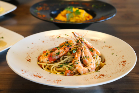 Spaghetti with shrimps, prawns, chopped basil and tomato on white plate.
