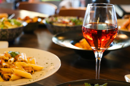 Wine rose in crystal glass with accompanying meal on wooden table.