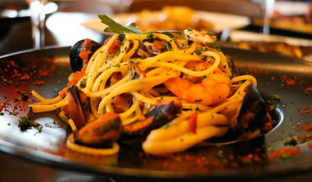 Spaghetti with shrimps, prawns, mussels and parsley on black plate.