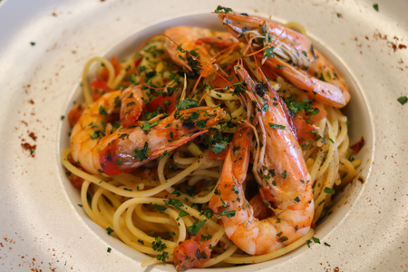 Spaghetti with shrimps, prawns, chopped parsley and tomato on white plate. Stock Photo