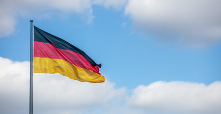 German flag waving on flagpole. Blue sky with few white clouds background, copyspace, banner. Stock Photo