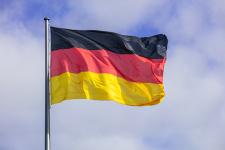 German flag waving on silver flagpole. Blue sky with many white clouds background. Stock Photo